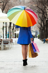 woman with purchases and umbrella
