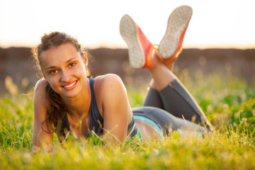 Young smiling woman resting after exercising