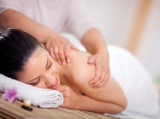 Beautiful woman having a wellness back massage at spa salon