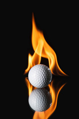 Golf ball on black background with fire
