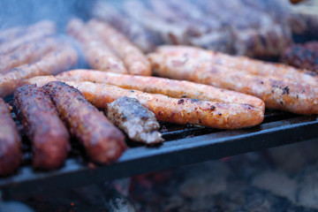 pork and beef sausages cooking over the hot coals on a barbecue