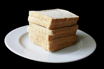 pile of slice bread rusks on white dish blurry black background