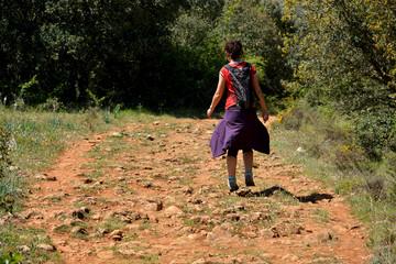mujer caminando por un camino de piedras