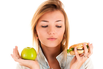 beautiful woman choosing between apple and hamburger