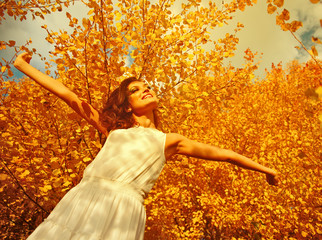 Young woman arms raised enjoying the fresh air in autumn forest
