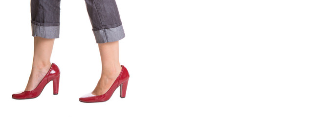 Woman legs with red heels over white background