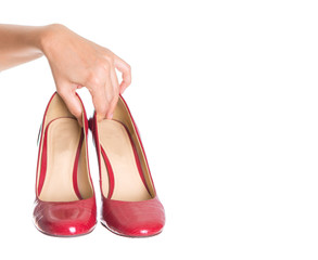 Female hand holding high heels over white background