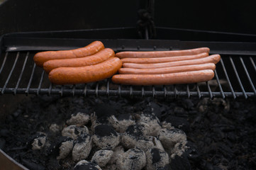 Sausages sizzles on charcoal