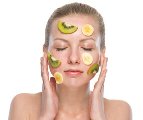 Young woman making fruit facial mask