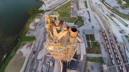 Aerial video smoke stack at industrial dig quarry site