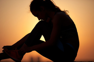 woman tying shoelaces against yellow sky at sunset