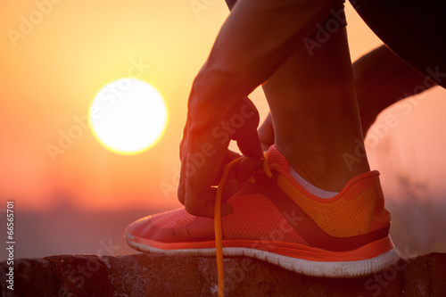canvas print picture woman tying shoelaces outdoor