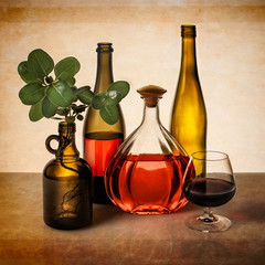 Still life with wine bottles and greenery