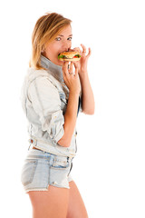 young woman eating a hamburger isolated on white background