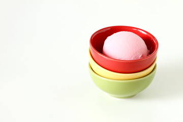 pink ice cream in a red ceramic cup on white background