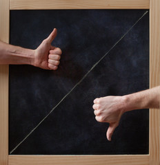 Thumbs up and down on blackboard