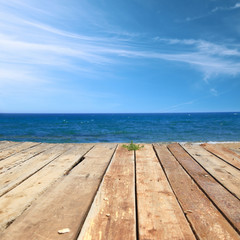 Wooden deck with sea and blue sky