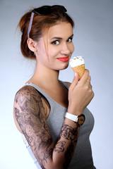 молодая девушка с татуировкой и рожком мороженого в руке
