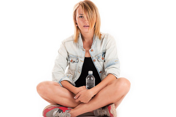 stylish woman sitting on the floor with a bottle in hand