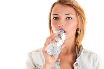 young girl drinks water from a bottle
