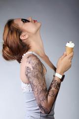 Молодая девушка в профиль на сером фоне с рожком мороженого