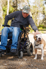 Young man in a wheelchair with his faithful dog .
