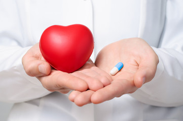 Doctor holding a heart and a pill