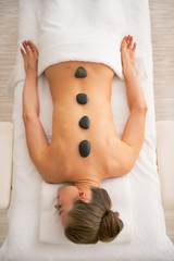 Relaxed woman laying on massage table and receiving hot stone