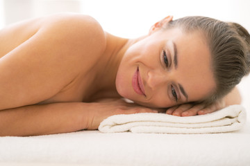 Happy young woman laying on massage table