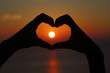 Golden sunset with hands silhouette in shape of heart - 66570391
