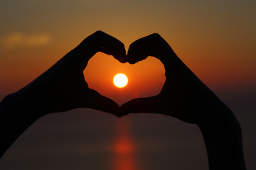 Golden sunset with hands silhouette in shape of heart