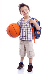 Happy school kid holding a basket ball, isolated on white backgr