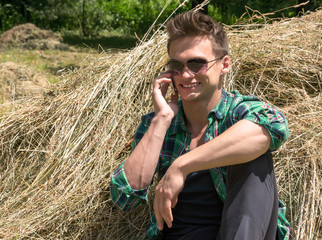 Young man talking on a cell phone while sitting in haystacks