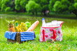Picnic basket with fruits, bread and bottle of white wine - 66573570