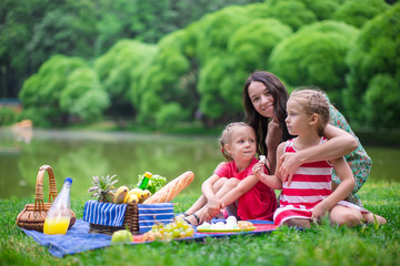 Adorable little girls and happy mother picnicking in the park