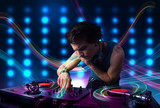 Young Dj mixing records with colorful lights poster