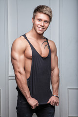 Muscular young sexy man posing in black t-shirt