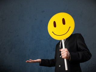 Businessman holding a smiley face emoticon