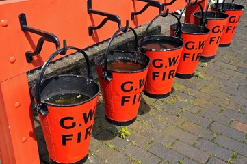 Red fire buckets at railway station © Arena Photo UK