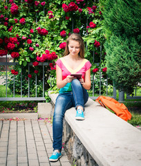 Pretty teenage student using digital tablet near a campus.