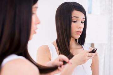 Examining her damaged hair.