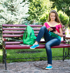 Student siting in a park on a bench and using tablet PC
