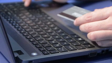Men using computer for on line purchase with credit card