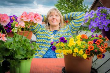 Frau auf dem Balkon mit Blumen