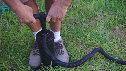 Man Using Air Pump on Grass