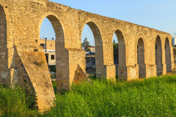 Old Greek aqueduct in warm sunset light in Larnaca, Cyprus