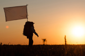 Hiker with backpack and flag walking in the field