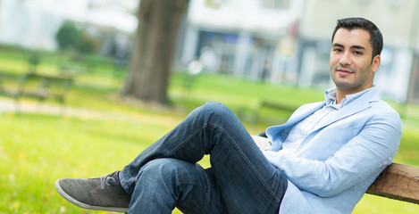 Young gorgeous man sitting on bench in a park,