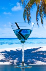 blue cocktail on beach on wood table