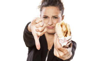girl holding a sandwich and showing thumbs down